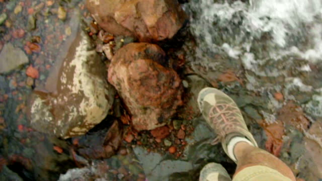 Close up of feet crossing stream video