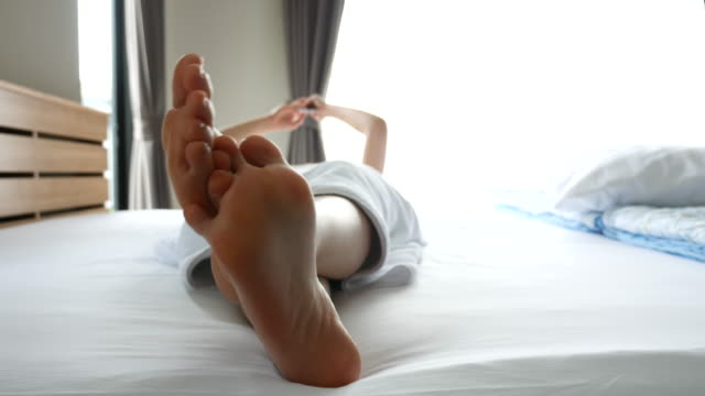 close up of female feet in bed, resting - scalzo video stock e b–roll