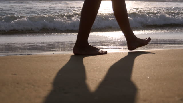 Close up of female feet walking on golden sand at the beach with ocean waves at background. Legs of young woman stepping at sand. Barefoot girl at the sea shore. Summer vacation holiday concept video