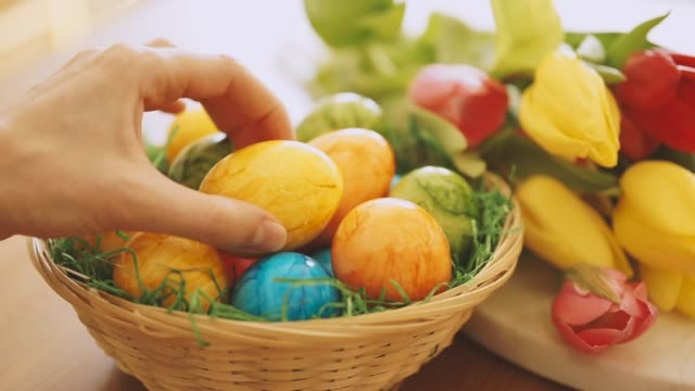close up of female hand putting an easter egg into a basket - pasqua video stock e b–roll