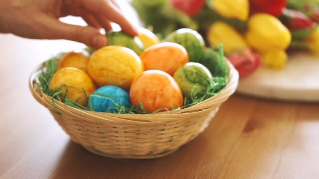Close up of female hand putting an Easter egg into a basket