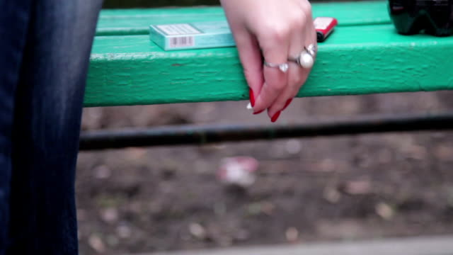 close up of female hand sticking chewing gum under the park bench - gum стоковые видео и кадры b-roll