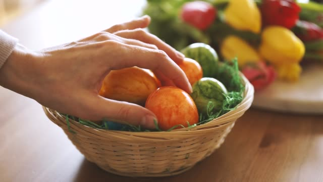 Close up of female hand taking an Easter egg from a basket