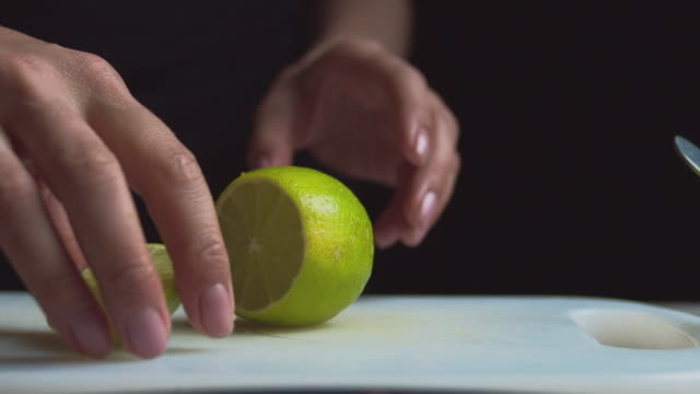 Close up of female hands on a dark background slices a lemon
