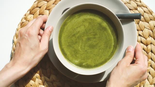 stockvideo's en b-roll-footage met close-up van de vrouwelijke handen zetten een kom spinazie soep op de tafel - groentesoep