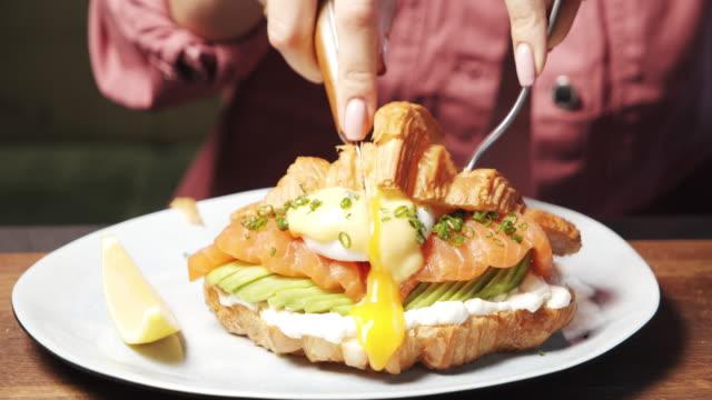 stockvideo's en b-roll-footage met sluit omhoog van vrouwelijke handen die een heerlijke croissant met kaas, avocado, plakjes zalm en gepocheerd ei met een mes snijden. lekker en gezond ontbijt. - geroosterd brood
