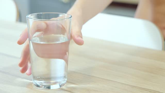 台所のテーブルからコップ一杯の水を取る女性の手を閉じます。 - グラス点の映像素材/bロール