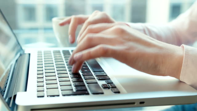 Close up of female hands using laptop computer, indoors.