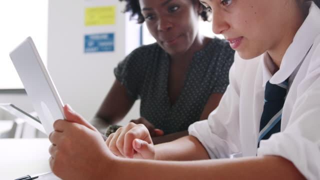 nahaufnahme von weiblich high school lehrer mit studentin tragen einheitliche verwendung digitaler tabletten für einzelunterricht im klassenzimmer - nachhilfelehrer stock-videos und b-roll-filmmaterial