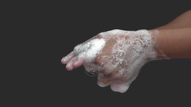 Close up of female lathering hands with soap before washing
