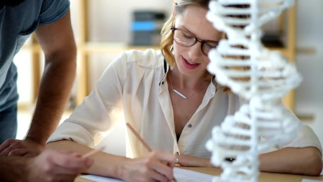 Close up of female student studying genetics with groupmate Up and coming professionals. Selective focus on a cheerful young girl wearing glasses listening to her friend and writing down necessary information while both examining a 3D DNA model and making homework together. biosensor stock videos & royalty-free footage