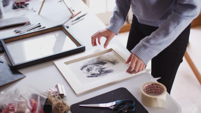 close up of female teenage artist framing picture in studio - rama obrazu filmów i materiałów b-roll