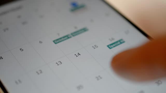 Close up of finger browsing through a smartphone calendar.