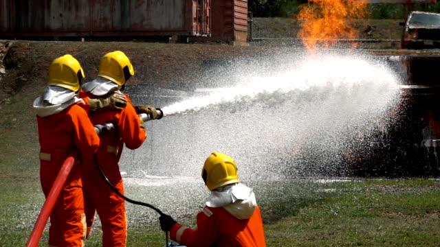Close Up Of Firefighters Fighting A Fire With Fire Hose And Foam Chemical To Extinguish A Fire Of Truck Accident