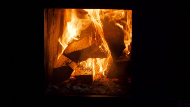 Close up of firewood burning in fires. A log fire crackling in the fireplace.