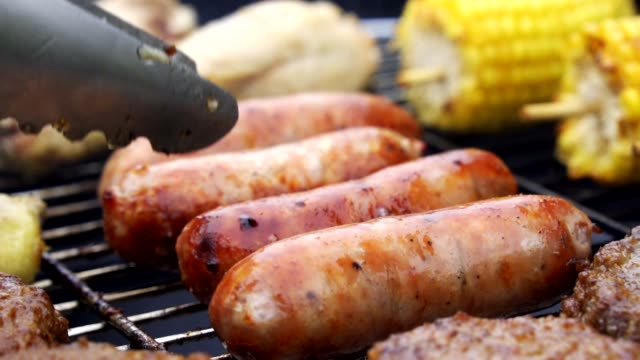 vídeos de stock, filmes e b-roll de feche acima das salsichas grelhadas da flama hamburgueres e galinha na grade ao ar livre do assado - salsicha