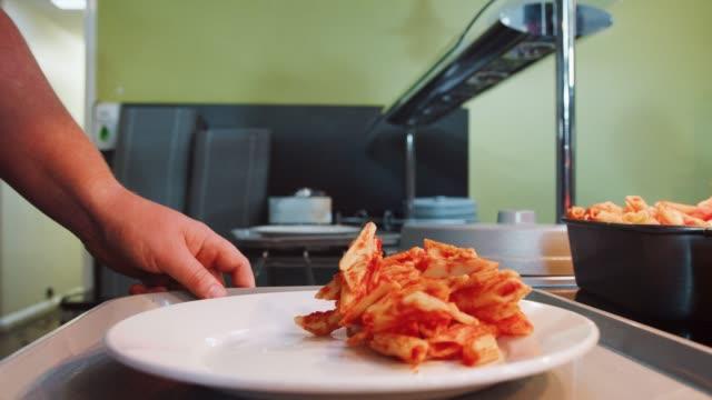 close up of food being served onto plate in canteen - stołówka filmów i materiałów b-roll