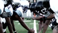 istock Close up of football players, linemen lining up and snapping the ball 684668994