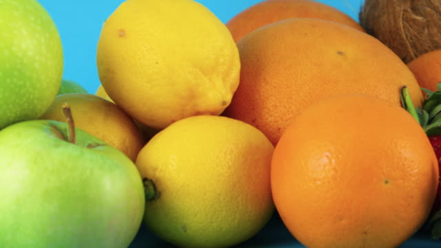 close up of fresh organic fruits pile on blue background - icon set healthy video stock e b–roll