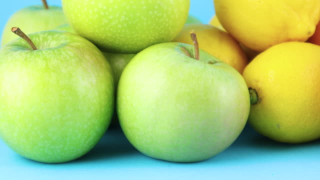 close up of fresh organic green apple and lemons on blue background - icon set healthy video stock e b–roll