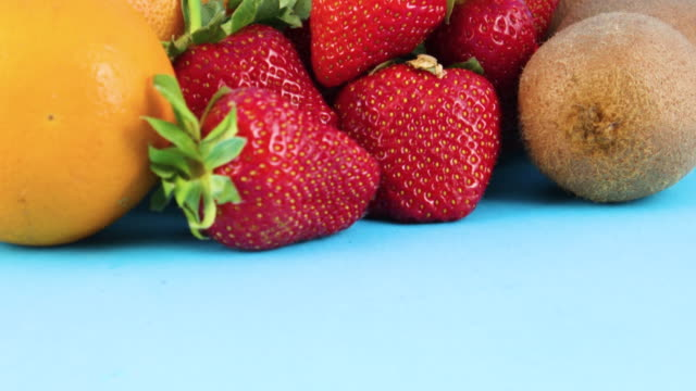 close up of fresh organic strawberries, oranges and kiwi on blue background - icon set healthy video stock e b–roll