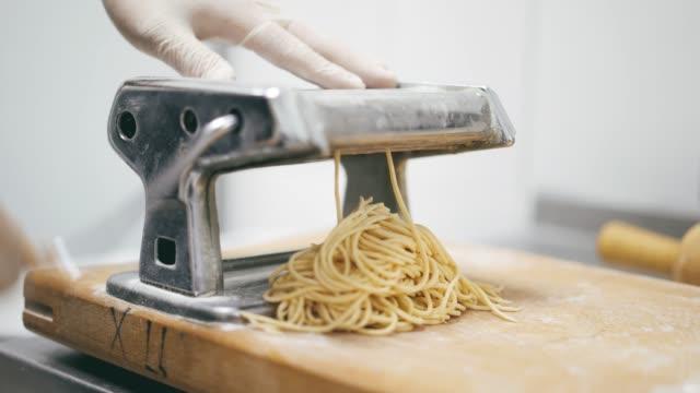 vídeos de stock, filmes e b-roll de feche acima de massa de espaguete fresco saindo de máquina de macarrão - comida italiana