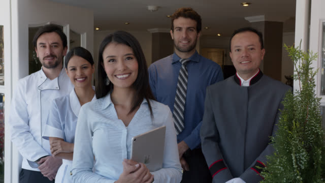 Close up of friendly team of workers at a hotel all facing camera smiling