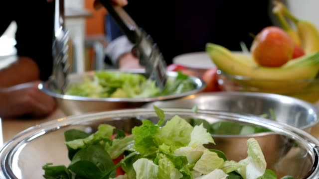 Close up of friends making salad from fresh vegetables in kitchen