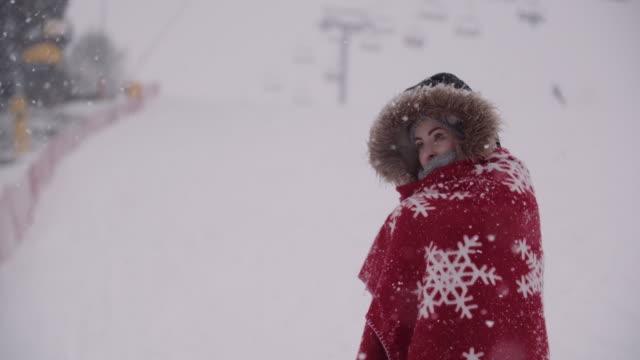 zbliżenie zamarzniętej kobiety owiniętej w koc na śnieżycę - drżeć filmów i materiałów b-roll