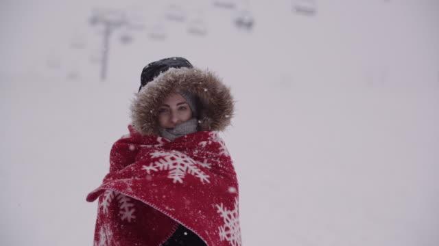крупный планом замороженные женщины, завернутые в одеяло на метель - шарф стоковые видео и кадры b-roll