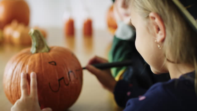 Close up of girl drawing on pumpkin