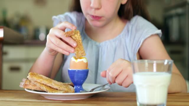 närbild på flicka äter friska kokt ägg och bruna rostat bröd till frukost i köket - kokat ägg bildbanksvideor och videomaterial från bakom kulisserna