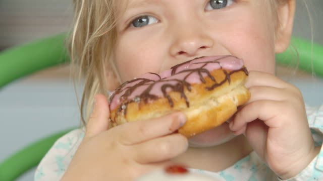 Close Up Of Girl Eating Iced Donut video