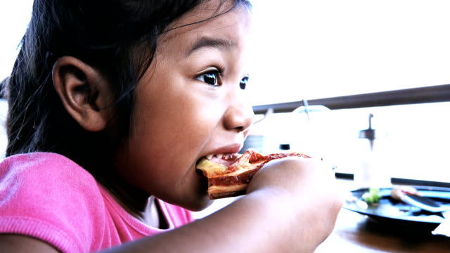 Close up of girl eating slice of pizza. video