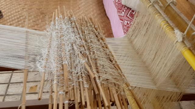 vidéos et rushes de gros plan de soie or sur métier à tisser, coton sur le métier à tisser manuel de bois dans la culture traditionnelle asiatique et main de femme tissent lifestyle - fibre