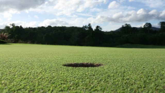 close up of golf ball rolling ing to the hole - foro video stock e b–roll