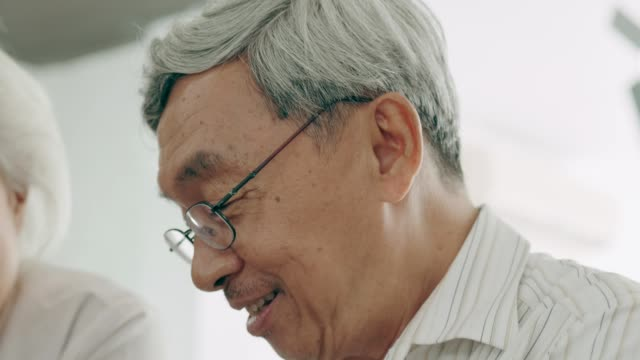 Close up of grandfather playing piano beside his wife video