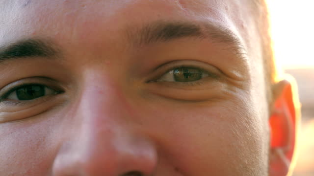 närbild av gröna ögon av en ung glad kille blinkar och tittar in i kameran mot bakgrund av bilar parkering. porträtt av stilig man stående i stadsmiljö och ler vid solnedgången. - male eyes bildbanksvideor och videomaterial från bakom kulisserna