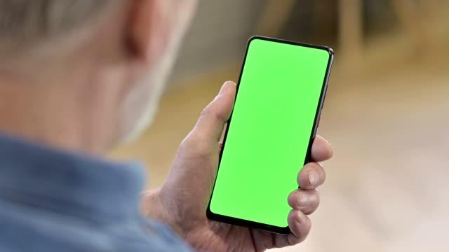 vidéos et rushes de fermez-vous vers le haut du smartphone vert d'écran de maquette - main humaine
