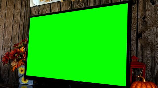 Close up of green screen HD / 4K TV in rustic fall decorated living room - includes reflection video