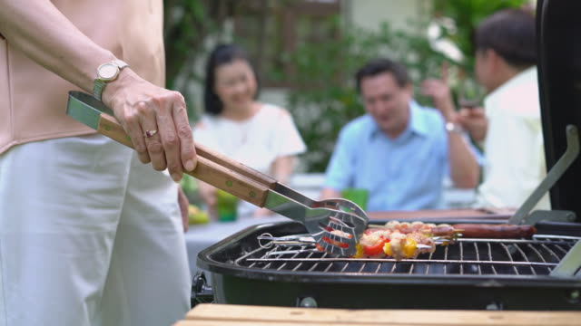Close up of Grilled barbecue with family in the garden.