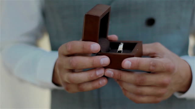 Close up of grooms hands holding and showing wooden box with pair of wedding rings video