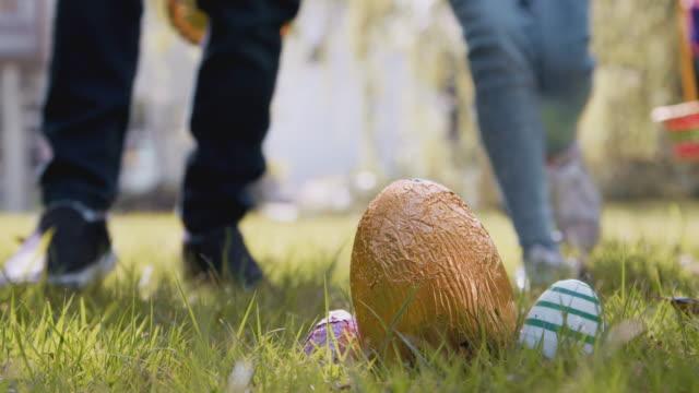 Close up of group of children on Easter egg hunt running across garden towards chocolate egg - shot in slow motion