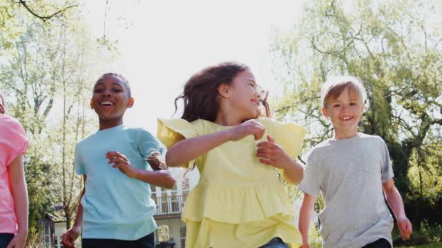 庭の芝生を横切って走り、カメラを見ている子供たちのグループのクローズアップ - スローモーションで撮影 - 男の子点の映像素材/bロール