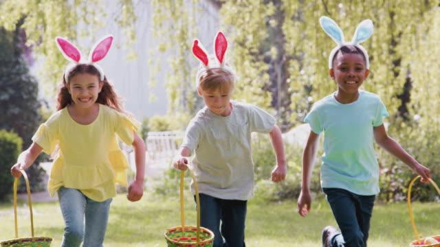 primo piano di un gruppo di bambini che indossano orecchie da coniglietto durante la caccia alle uova di pasqua che attraversano il giardino verso - girato al rallentatore - easter video stock e b–roll