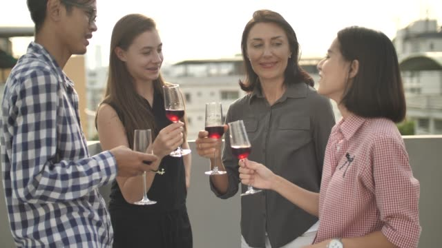 close up of group of friends toasting with red wine on rooftop - office party stock videos and b-roll footage