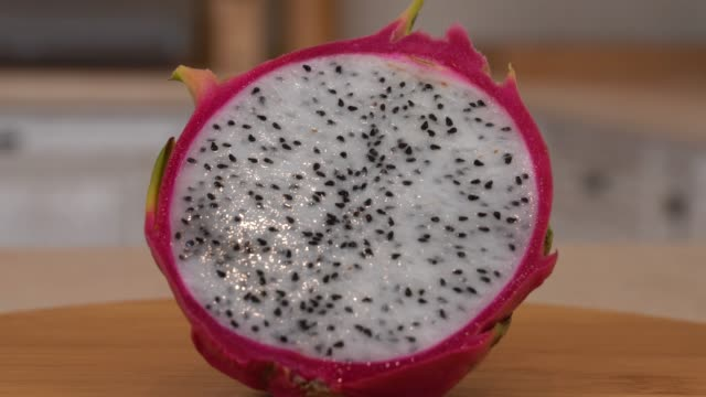 Close up of half slice of fresh dragon (pitahaya). Slowly rotating camera with white kitchen on the background. Dolly-shot. video