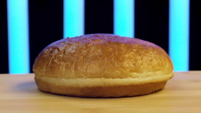 Close up of hamburger bun cut in two. Stock footage. Wheat burger bun lying on wooden surface with flying flour on black background with blue stripes