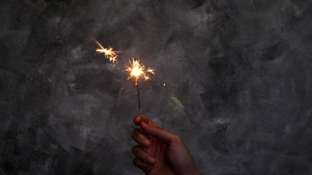 Close up of hand holding sparkler on grunge background, holiday concept video