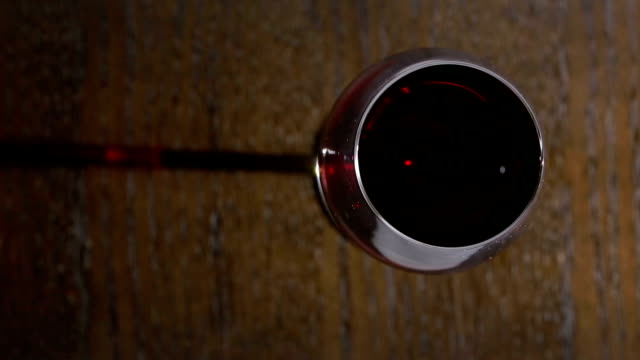 Close up of hand of sommelier holding a glass of red wine. video